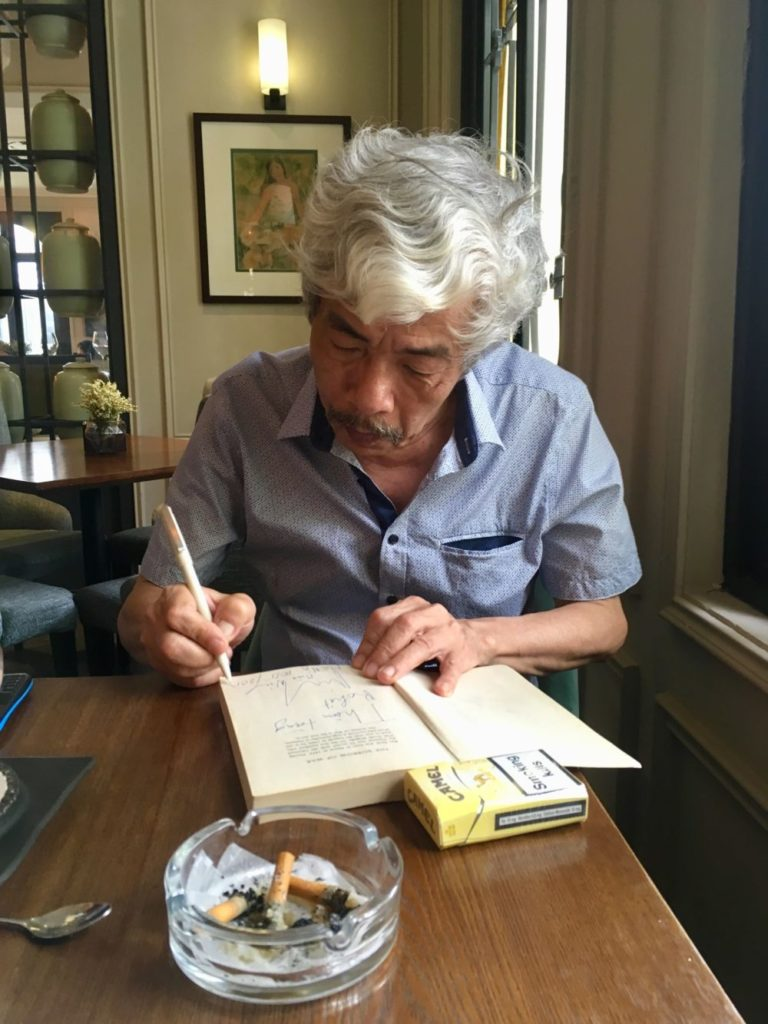 Bao Ninh signing copy of The Sorrow of War. Hanoi, 2018. photo: Rohit Iniani