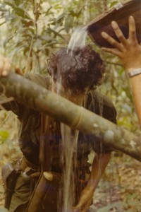 Medic gets water poured on head. Song Be, Vietnam 1970