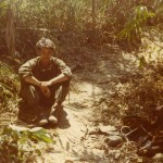Medic sitting on well-used trail. Song Be, Vietnam 1970