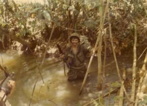 Gary Williams crossing stream. Song Be, Vietnam 1970