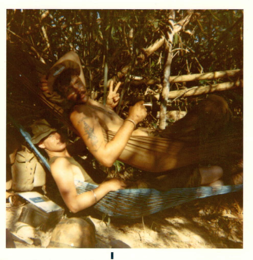 Jeff (in blue hammock) with squad leader and friend Gary Kelch (smoking a joint and giving V sign). Most grunts wore Montangard bracelets like the one Gary wears on his wrist. Jeff''s was lost after he was wounded. Gary visited Jeff at 24th Evac. He removed his bracelet and gave it to Jeff. Song Be, Vietnam 1970