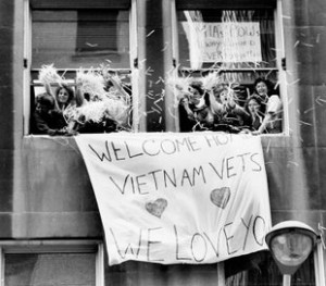 "Tens of thousands of Vietnam War veterans today formed the biggest parade in the city's history, marching across the Brooklyn Bridge and down Broadway in a lavish ticker-tape ""welcome home"" that was 10 years late.  Tons of ticker tape and confetti, obliterating street signs in a blizzard of white, showered down on the 25,000 veterans as they wound through the financial district at the lower tip of Manhattan. Brooklyn, 1985"