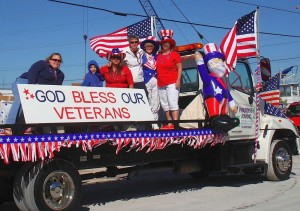 Veterans Day parade tow truck with sign, flag, civilians.